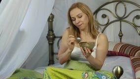 A menina loura alegre da mulher acordou e comendo uma salada deliciosa em uma cama, café da manhã saudável 4K vídeos de arquivo