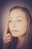 A menina loura aplica o creme, efeito da grão fotografia de stock