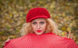 Menina loura atrativa com o tampão vermelho que olha sobre o tiro exterior do guarda-chuva vermelho. Jovem mulher atrativa em um t Imagens de Stock
