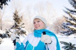 A menina loura atrativa com os polos de esqui nas mãos com um sorriso olha Foto de Stock Royalty Free