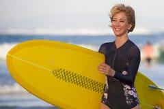 Menina loura atrativa e feliz nova do surfista na praia bonita que leva a placa de ressaca amarela que anda fora da água que apre imagem de stock