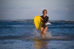 Menina loura atrativa e feliz nova do surfista na praia bonita que leva a placa de ressaca amarela que anda fora da água que apre fotos de stock