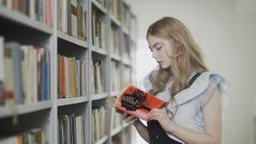 Menina loura atrativa nova do estudante que toma dois livros da prateleira na biblioteca video estoque