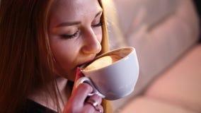 A menina loura bebe o café e a conversa no telefone, sentando-se em um sofá bege na definição 4k no movimento lento vídeos de arquivo