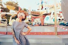 A menina loura bonita com corte de cabelo curto está levantando no parque de diversões no fundo do carrossel Veste o vestido quad fotos de stock royalty free