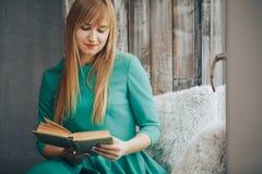 Menina loura bonita com um livro em suas mãos que olham para fora a janela imagens de stock