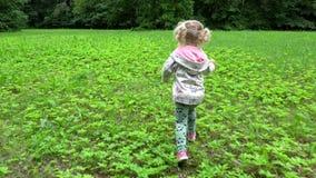 A menina loura bonita corre através do prado no parque A criança bonita tem o divertimento fora video estoque