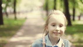 Menina loura bonita da escola que anda em um parque do verão video estoque