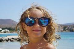 A menina loura bonita de 3-4 anos sorri felizmente durante os feriados em Paros imagens de stock royalty free