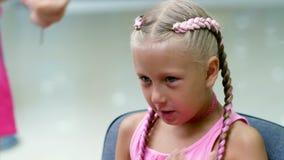 A menina loura bonita, de sete anos velho, trançou duas tranças, faz um penteado com os fechamentos cor-de-rosa do cabelo em um s vídeos de arquivo