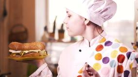Menina loura bonita do cozinheiro dos jovens com Hamburger 4K video estoque