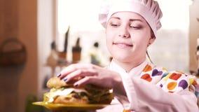 Menina loura bonita do cozinheiro dos jovens com Hamburger 4K vídeos de arquivo