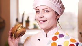 Menina loura bonita do cozinheiro dos jovens com Hamburger 4K filme
