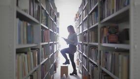 Menina loura bonita do estudante que toma o livro da prateleira na biblioteca da universidade filme
