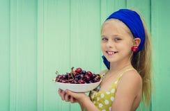 Menina loura bonita em um fundo da parede de turquesa que guarda a placa com cereja fotografia de stock royalty free
