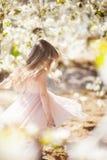 Menina loura bonita em um pomar de cereja de florescência Imagens de Stock Royalty Free