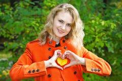 A menina loura bonita em um revestimento vermelho mostra o coração imagem de stock royalty free