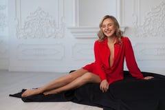A menina loura bonita em uma camisa vermelha no interior branco senta-se no assoalho em um pano preto fotos de stock