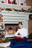 Menina loura bonita em uma saia azul que senta-se perto do Natal Imagem de Stock