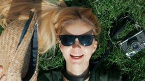 A menina loura bonita encontra-se na grama e engana-se ao redor decola e põe sobre um chapéu que encontra-se sobre a grama Concei vídeos de arquivo