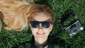 A menina loura bonita encontra-se na grama e engana-se ao redor decola e põe sobre um chapéu que encontra-se sobre a grama Concei video estoque