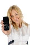 A menina loura bonita mostra o telefone celular foto de stock