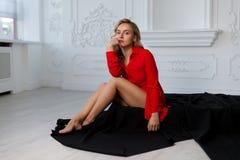 A menina loura bonita na camisa vermelha no interior branco senta-se no assoalho em um pano preto imagens de stock royalty free