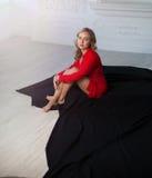 A menina loura bonita na camisa vermelha no interior branco senta-se no assoalho em um pano preto imagens de stock