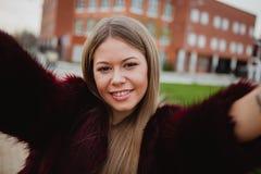 Menina loura bonita no parque que faz-se uma foto Imagem de Stock