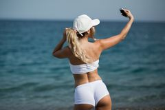 A menina loura bonita no sportwear na praia faz o selfie imagem de stock royalty free