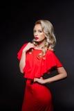 Menina loura bonita no vestido de noite vermelho sobre o fundo cinzento Fotos de Stock Royalty Free