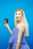 Menina loura bonita no vestido listrado verão com a câmera retro no fundo azul no estúdio Imagens de Stock
