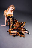 Menina loura bonita no vestido no assoalho Imagem de Stock Royalty Free