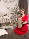 Menina loura bonita no vestido vermelho e nos presentes do ano novo Humor e interior do ano novo Imagens de Stock Royalty Free