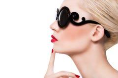 Menina loura bonita nos óculos de sol com os bordos vermelhos no backg branco Imagens de Stock Royalty Free
