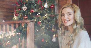 Menina loura bonita nova com cabelo encaracolado que sorri e que olha a árvore de Natal video estoque