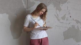 Menina loura bonita nova com cores de mistura da escova na paleta Arte, faculdade criadora, conceito do passatempo vídeos de arquivo