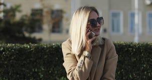 A menina loura bonita nova na roupa ocasional e os óculos de sol que sentam-se em um banco em uma cidade estacionam vídeos de arquivo