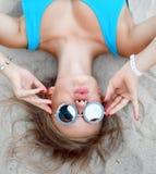 Menina loura bonita nova que encontra-se na areia tropical na praia tropical na veste azul do corpo e no beijo redondo dos óculos fotos de stock royalty free