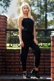 Menina loura bonita nova que levanta no fundo da paisagem urbana Senhora 'sexy' em um vestido preto foto de stock royalty free