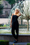Menina loura bonita nova que levanta no fundo da paisagem urbana Senhora 'sexy' em um vestido preto com uma aparência agradável foto de stock