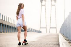 Menina loura bonita nova que monta o skate brilhante na ponte Fotografia de Stock