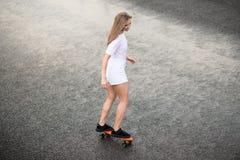 Menina loura bonita nova que monta o skate brilhante na ponte Foto de Stock Royalty Free