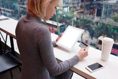 A menina loura bonita nova usa o portátil e o telefone quando a tela de trabalho da viagem conectou ao Internet 4G na cafetaria Fotos de Stock