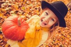 Menina loura bonita pequena com a abóbora grande no fundo do outono fotos de stock