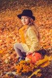 Menina loura bonita pequena com a abóbora grande no fundo do outono foto de stock