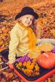 Menina loura bonita pequena com a abóbora grande no fundo do outono fotografia de stock
