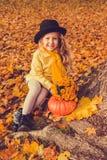 Menina loura bonita pequena com a abóbora grande no fundo do outono imagens de stock royalty free