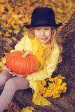 Menina loura bonita pequena com a abóbora grande no fundo do outono foto de stock royalty free