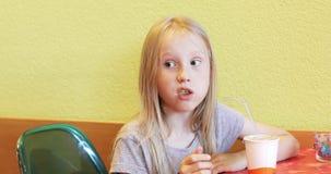 Menina loura bonita que come fritadas das batatas video estoque